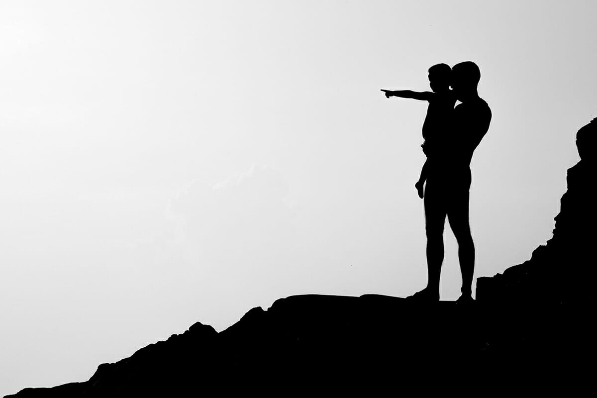 Father and Son on hill silhouette